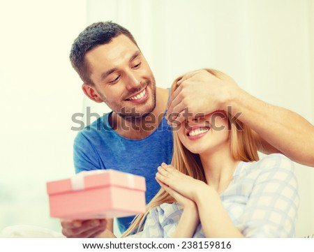 love, holiday, celebration and family concept - smiling man surprises his girlfriend with present at home - stock photo