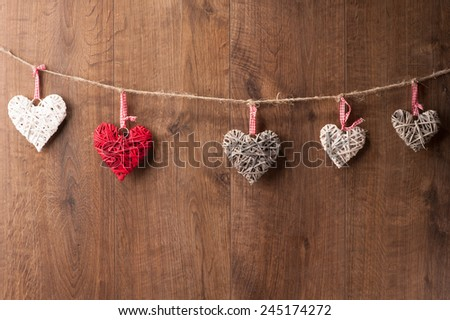 Love is in the air. Closeup image of original composition made of decorative hearts hanging on the wooden wall - stock photo