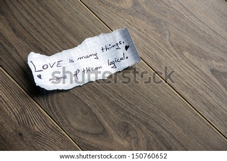 Love is many things, none of them logical (Quote by William Goldman) - Hand writing text on a piece of paper on wood background with space for text - stock photo