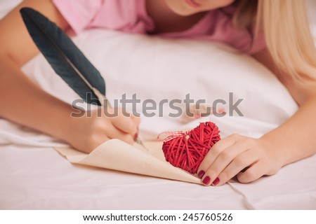 Love letter. Closeup image of woman writing a vintage letter to valentines day with feather pen while lying in bed and holding souvenir heart - stock photo