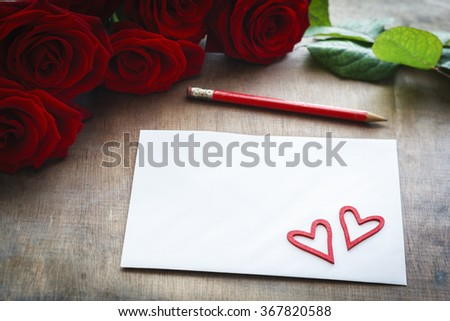 love letter in front of bunch of red roses