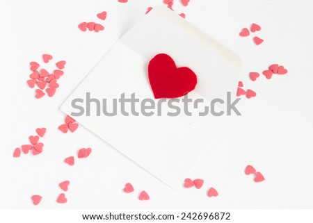 Love letter with a red heart symbol inside and heart-shaped candies around, on a white background. - stock photo
