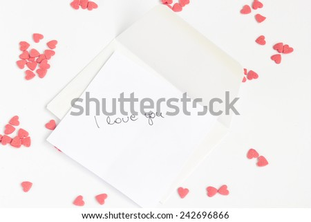 Love letter with heart shaped candies around, on a white background. - stock photo