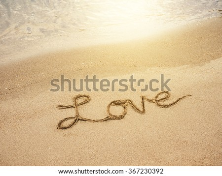 Love lettering message written on Sand Beach background with sunrise - stock photo