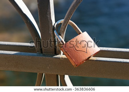 Love lock engraved with a heart to signify commitment and lifelong love locked on a wrought iron railing or balustrade, a trendy fad by tourists considered an act of vandalism by town authorities - stock photo