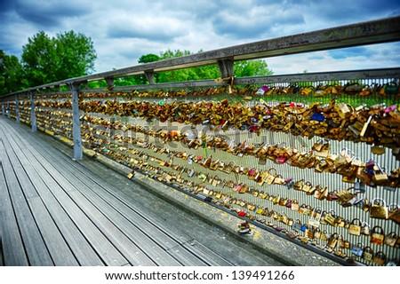 Love locks on Paris bridge at cloudy summer day - stock photo
