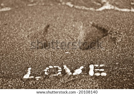 Love message written by white stones on a beach sand and footprints - stock photo