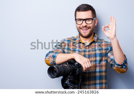 Love my job. Portrait of confident young man in shirt holding hand on camera on tripod and gesturing while standing against grey background - stock photo