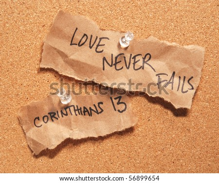 Love Never Fails written on scraps of wrinkled brown bag pinned to a corkboard - stock photo