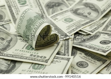 love of money heart shaped 100 dollar bill on pile of 100 dollar bills - stock photo