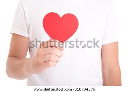 love or health care concept - young man holding red paper heart