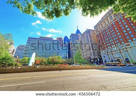 Love Park and Penn Center with skyline of skyscrapers in Philadelphia, Pennsylvania, USA. It is central business district in Philadelphia. Tourists in the street - stock photo