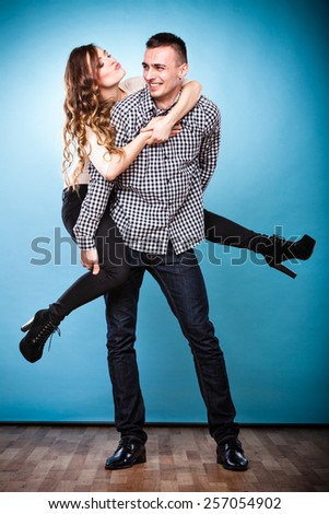 Love people and happiness concept. Smiling young couple having fun, man giving piggyback ride to woman studio shot on blue - stock photo