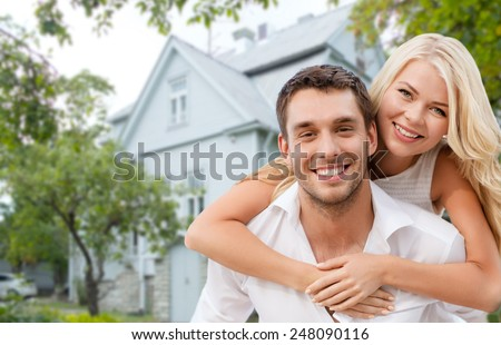 love, people, real estate, home and family concept - smiling couple hugging over house background - stock photo