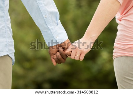 Love, rear view of an interracial couple. - stock photo