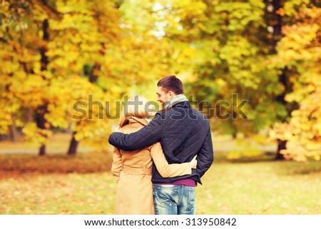 love, relationship, family and people concept - smiling couple hugging in autumn park from back - stock photo