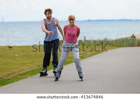 Love romance fitness sport relax leisure active concept. Teens together on skating date. Girl and boy riding together on rollerblades through seafront park. - stock photo