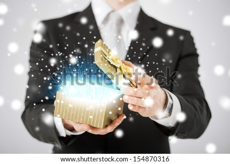 love, romance, holiday, celebration concept - man opening gift box - stock photo