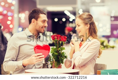 love, romance, valentines day, couple and people concept - happy young man with red flowers giving present to smiling woman at cafe in mall