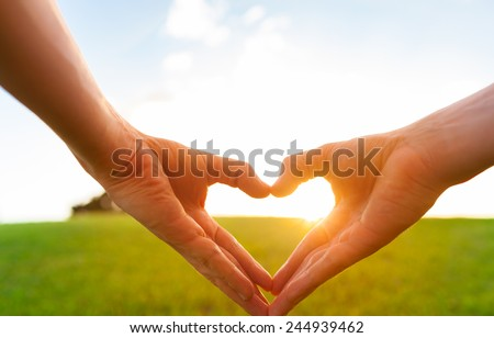 Love shape hands against natural background - stock photo