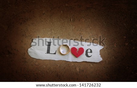 Love spelled with a gold wedding ring and red broken heart - stock photo