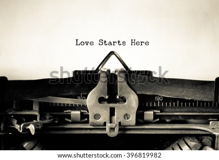Love Starts Here word  typed on a Vintage Typewriter.   - stock photo