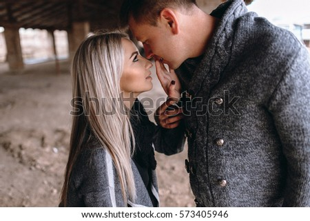 love story of a beautiful couple. walking and posing beside an old brick house. gentle portrait. touch the fingers