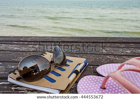 love summer decorate with eyeglasses and recycle note book with pink dot slipper on wooden plate over blue sea background,summer holiday travel concept. - stock photo