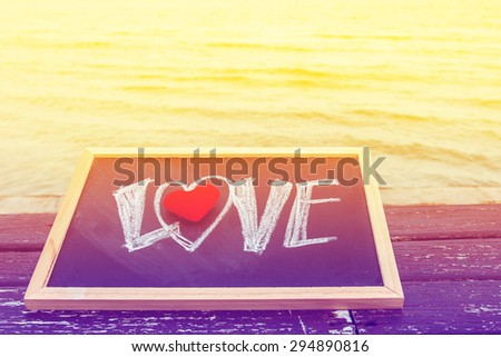 love summer decorate with heart and chalkboard on wooden floor on the blue sea,,vintage color filter - stock photo