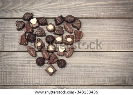 Love symbol full of chocolate candies - stock photo