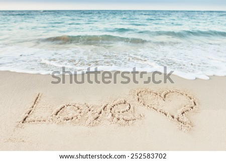 Love text and heart drawn on sand by sea at beach - stock photo