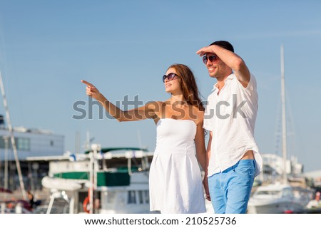 love, travel, tourism and people concept - smiling couple wearing sunglasses walking at harbor and pointing finger