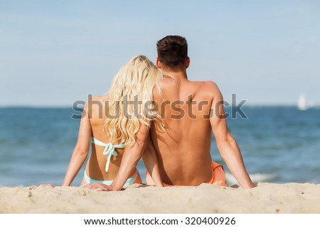 love, travel, tourism, summer and people concept - smiling couple on vacation in swimwear sitting on beach from back - stock photo