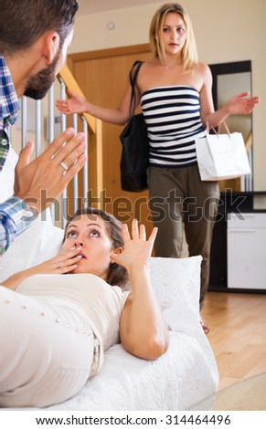 Love triangle: husband, despair wife and unhappy lover at home interior - stock photo