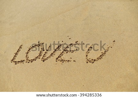 Love U sign on the sand beach copy space texture background outdoors