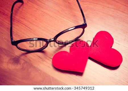 Love valentine concept. Two hearts with eyeglasses on wood table. Retro filter - stock photo