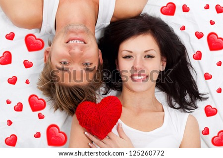 love valentine day couple holding red heart young lovely together lying in a bed, happy smile looking at camera, concept hearts flying around - stock photo