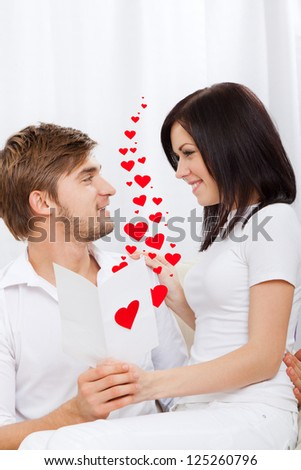 love valentine day couple valentine's greeting card, note, letter with red heart, happy smile looking to each other, sitting on coach, concept hearts flying around - stock photo