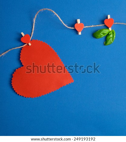 Love Valentine's hearts natural cord and red clips on blue background, copy space - stock photo