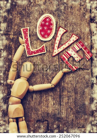Love valentines day background, letters forming word LOVE written on wooden background, wooden man holding love letters on wooden background - stock photo