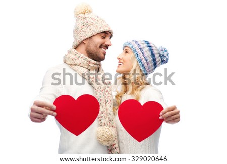 love, valentines day, couple, christmas and people concept - smiling man and woman in winter hats and scarf holding red paper heart shapes - stock photo