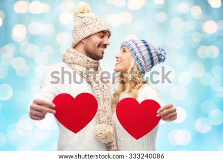 love, valentines day, couple, christmas and people concept - smiling man and woman in winter hats and scarf holding red paper heart shapes over blue holidays lights background - stock photo