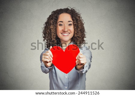 Love valentines day woman holding giving you red heart. Smiling cute happy adorable curly hair girl isolated on grey wall background. Positive human face expression emotion feeling life perception  - stock photo