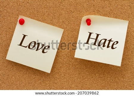Love versus Hate, Two yellow sticky notes on a cork board with the words Love and Hate - stock photo