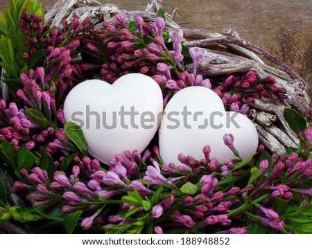 Love white hearts with lilac blossoms in wreath on wooden background - stock photo