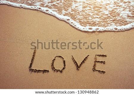 love, word drawn on the beach - stock photo