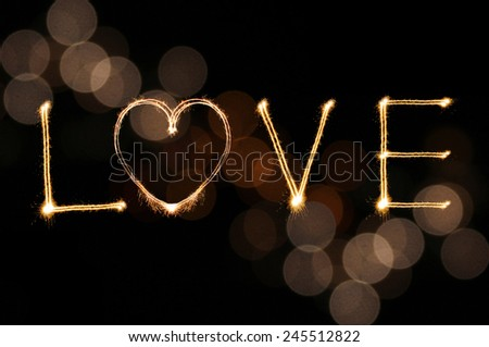 Love writing by sparkler firework on gold defocused bokeh background for Valentines day - stock photo