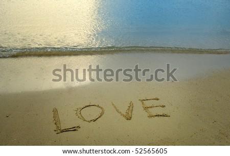 Love written in sandy beach - stock photo