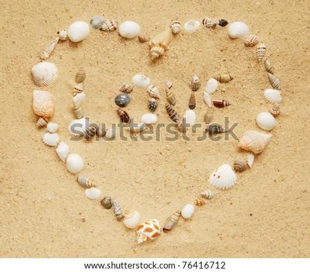 love written in small shells inside a heart made of seashells - stock photo