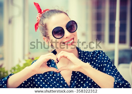 Love you. Portrait close up happy smiling young woman showing heart sign gesture with hands isolated restaurant coffee shop background. Positive human emotion expression feeling attitude body language - stock photo